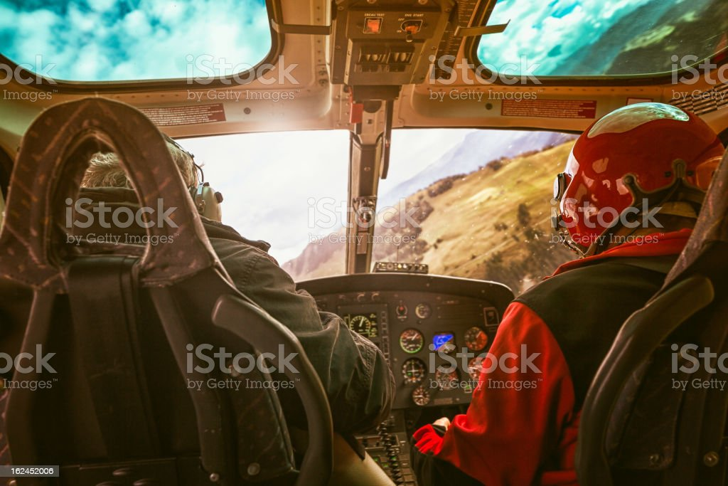 In Flight Helicopter cockpit with pilot flying over Switzerland stock photo