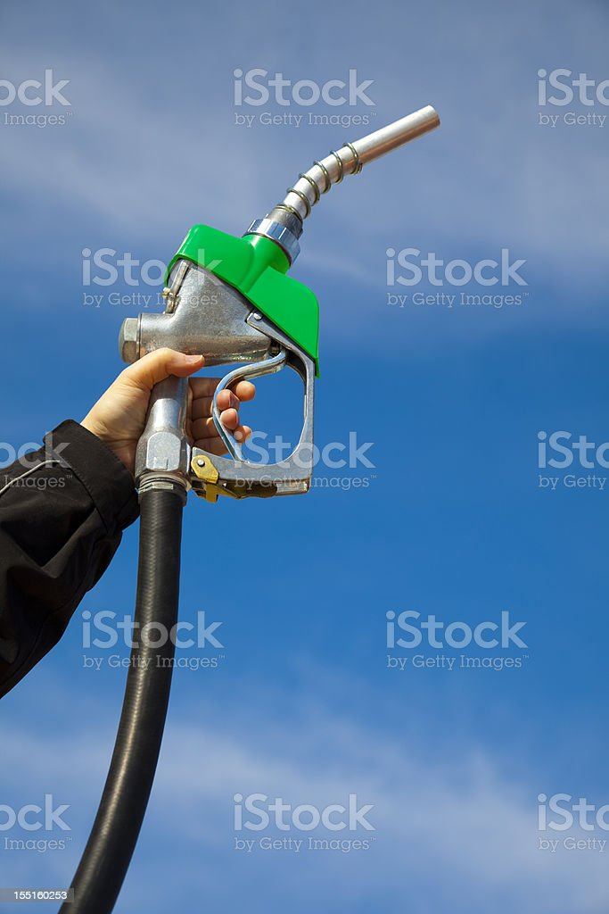 In Gas We Trust; Gasoline Pump Nozzle Held Toward Sky stock photo