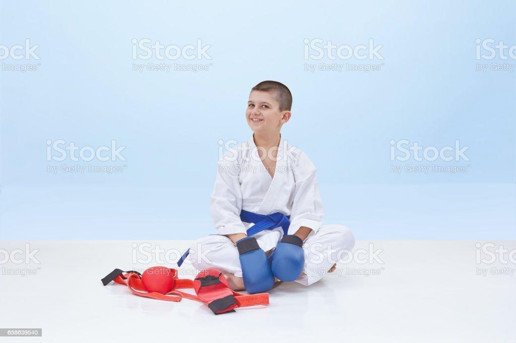 In karategi boy sits near karate outfit stock photo