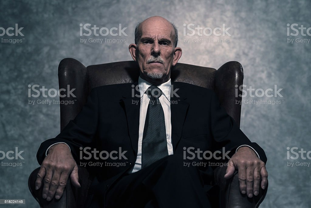 In leather chair sitting senior businessman with gray beard. stock photo