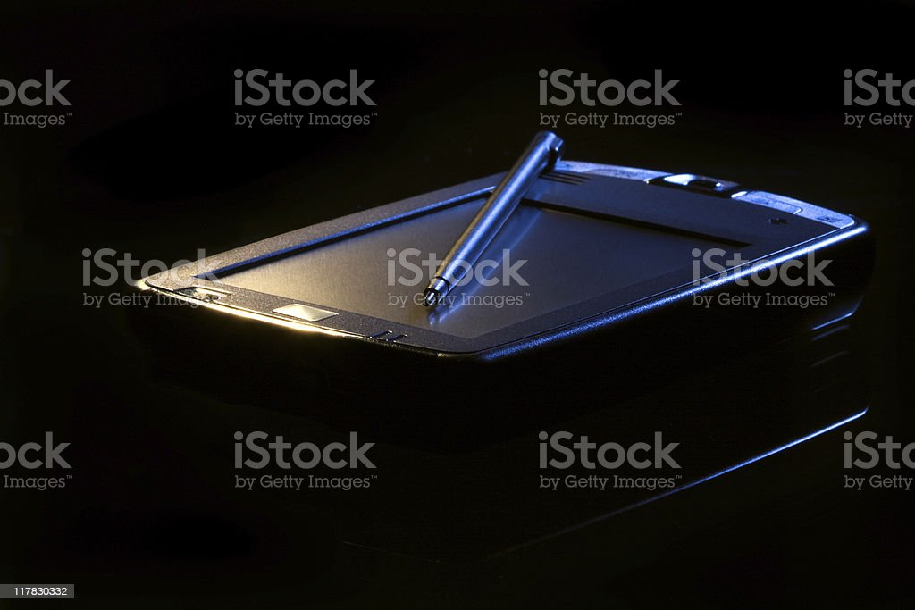 PDA in light beam. Black background. royalty-free stock photo