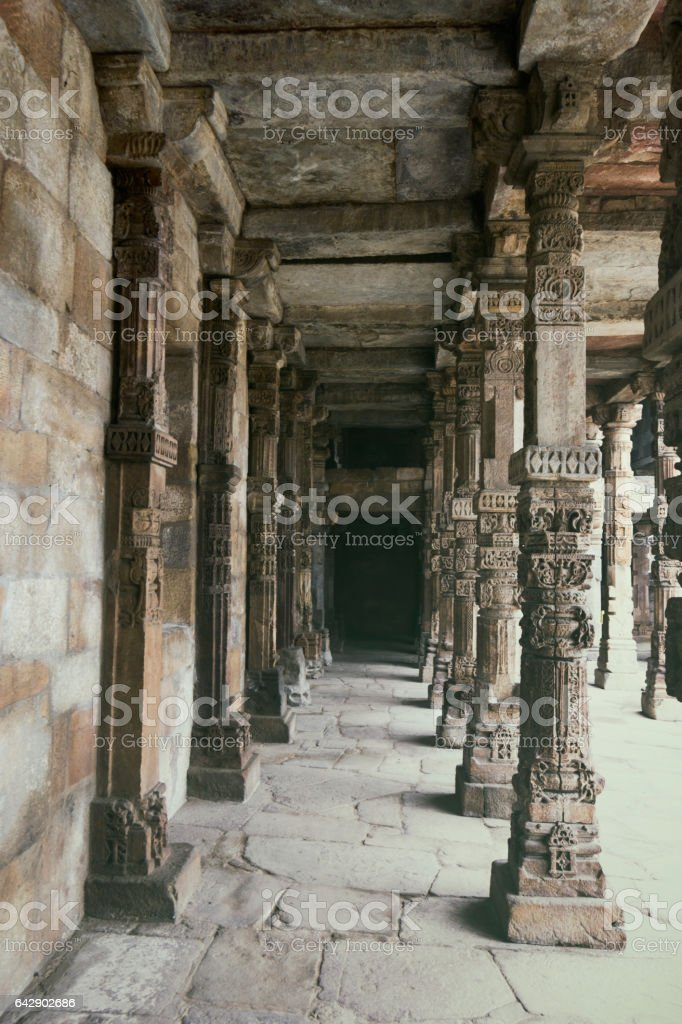 In New Delhi, India, Qutub Minar architectural details such as carved columns and stone flooring and walls stock photo
