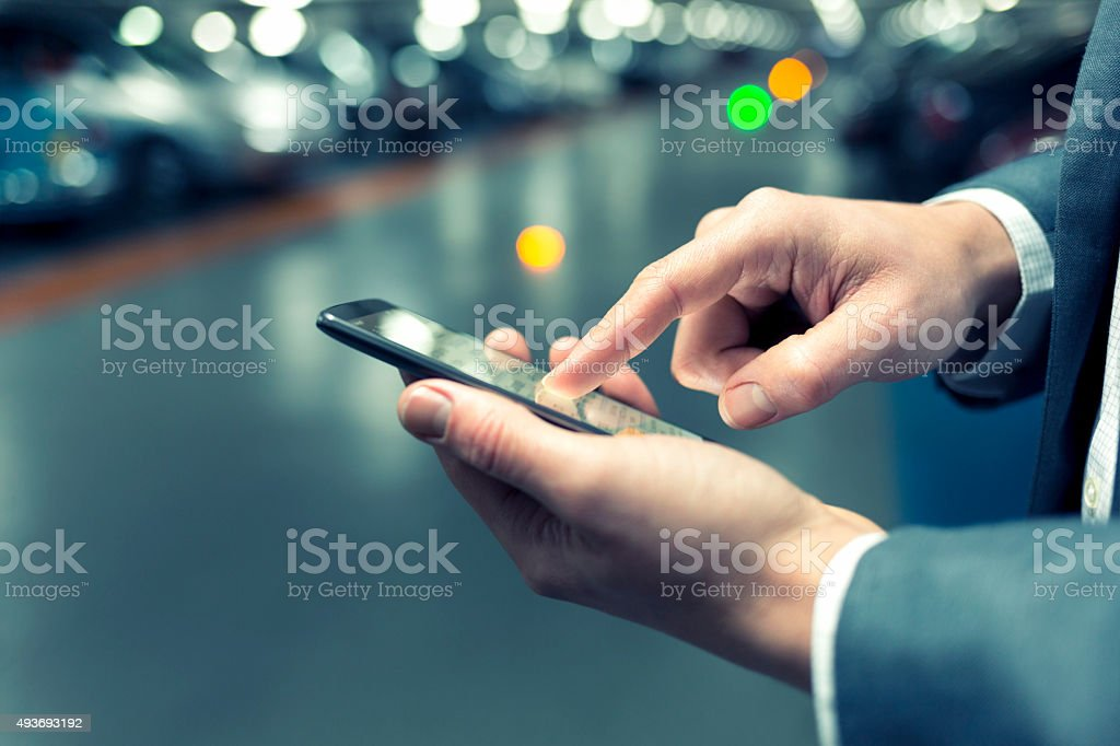 In parking lot a man using mobile phone. Light bokeh stock photo
