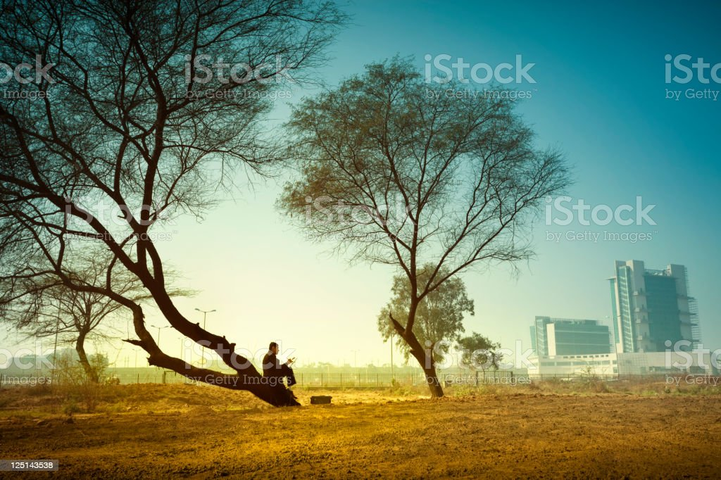 In rural landscape businessman sitting far from city under tree stock photo