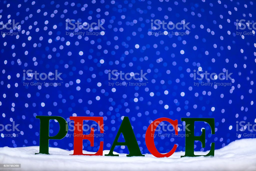 PEACE in snow with bokeh starry sky background stock photo