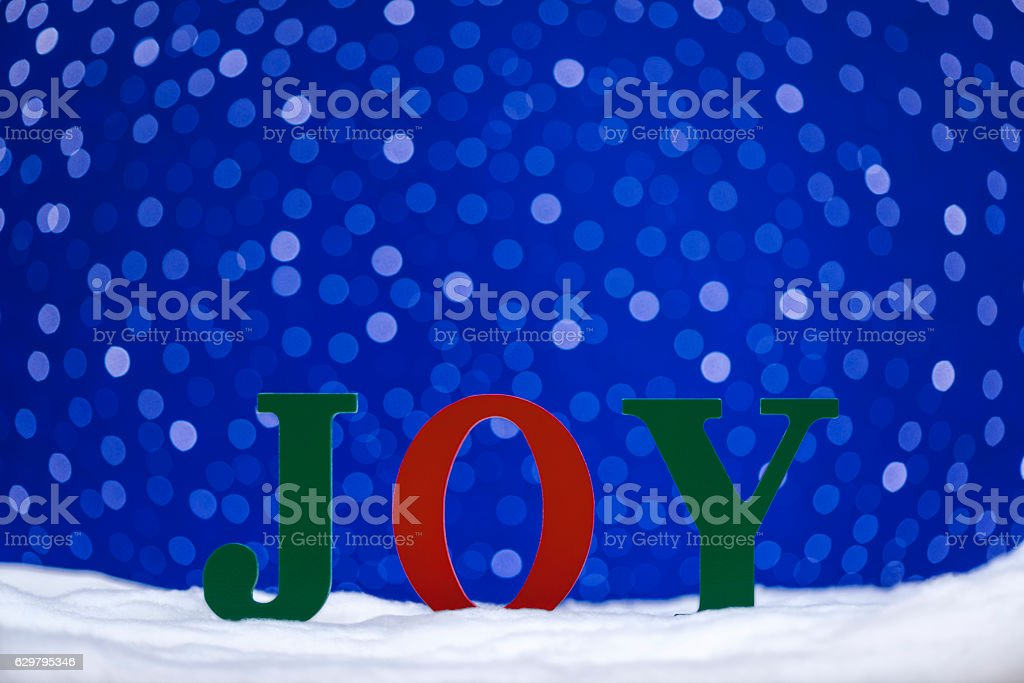 JOY in snow with bokeh starry sky background stock photo
