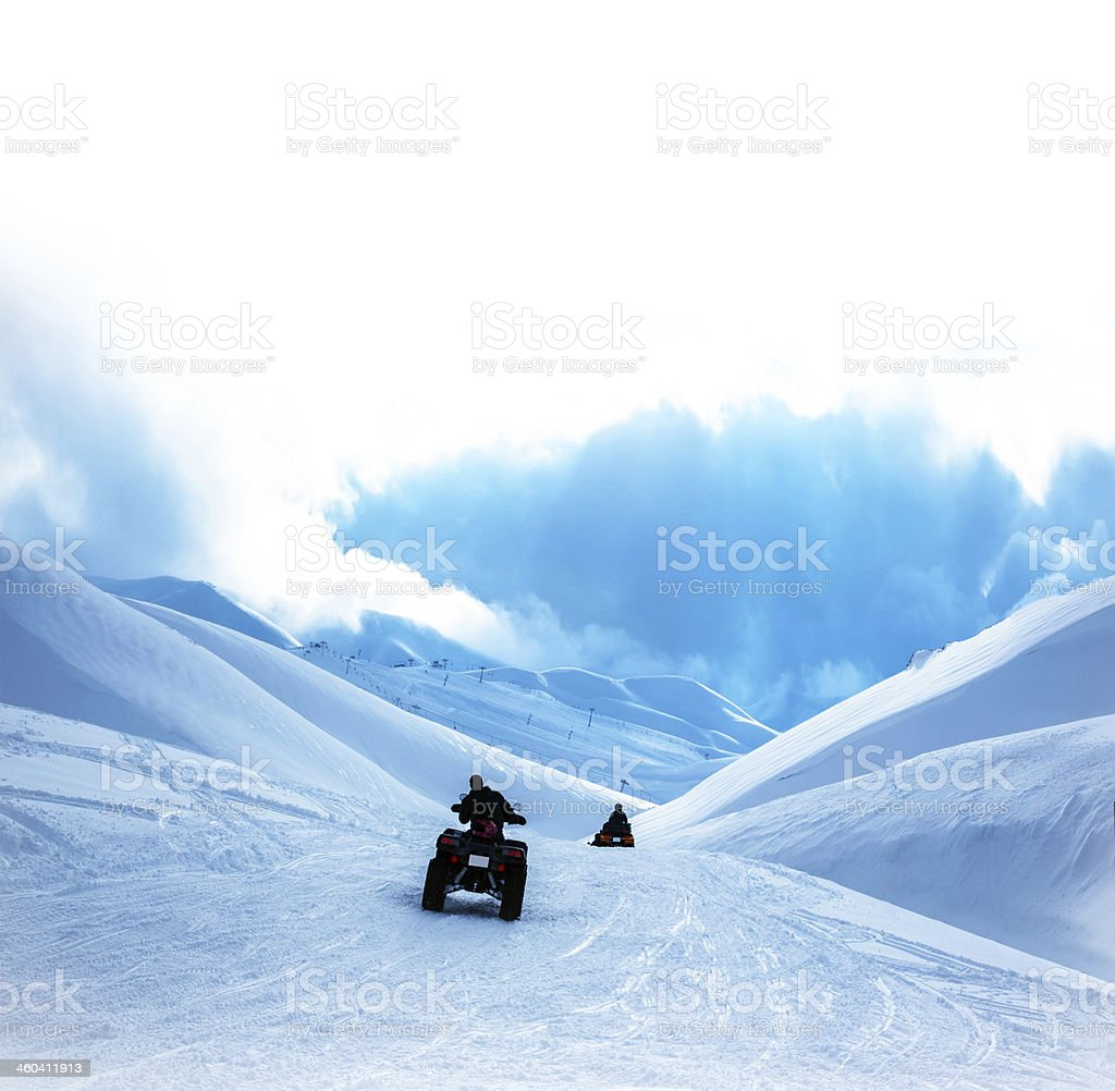 ATV in snowy mountains royalty-free stock photo