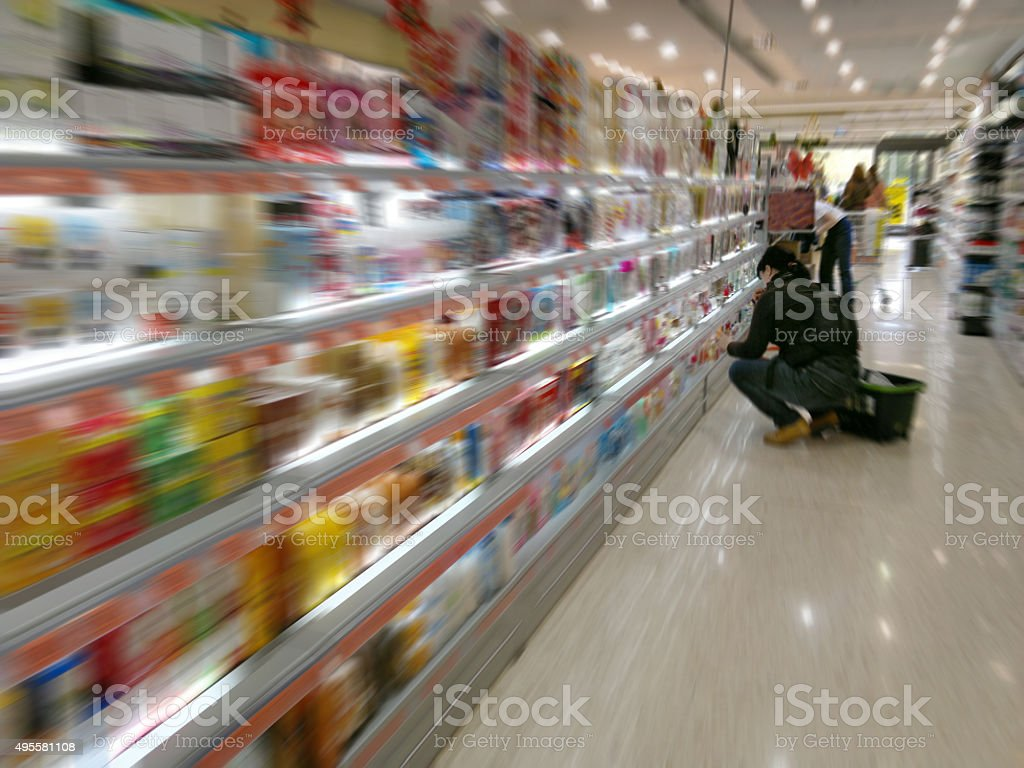 In Supermarket at a shelf with colorful goods stock photo