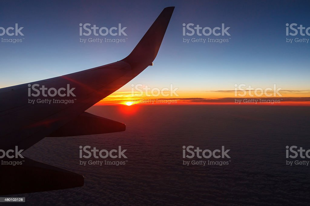In the air - airplane wing at sunset background stock photo
