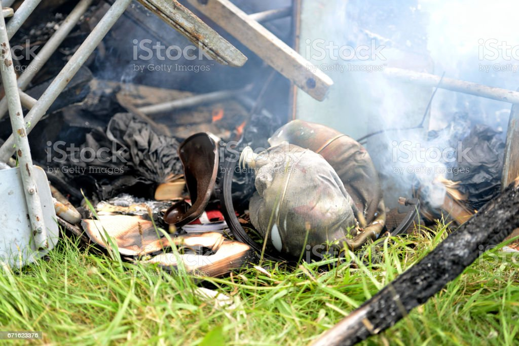 In the grass lying fire damaged things and books.