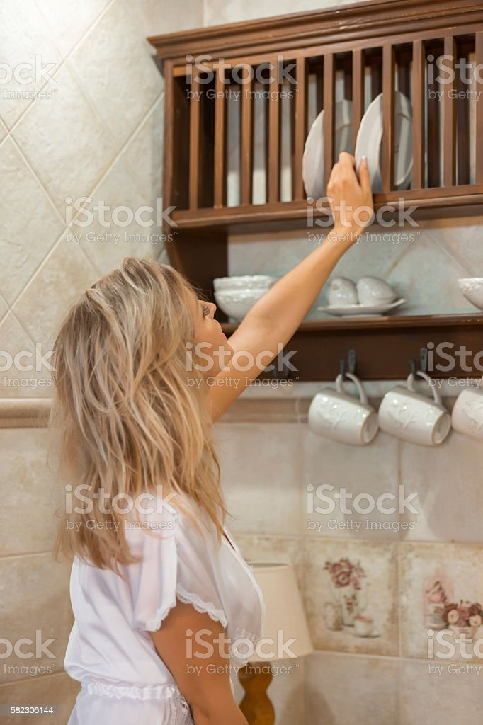 In the kitchen. Young woman taking plate from rack stock photo