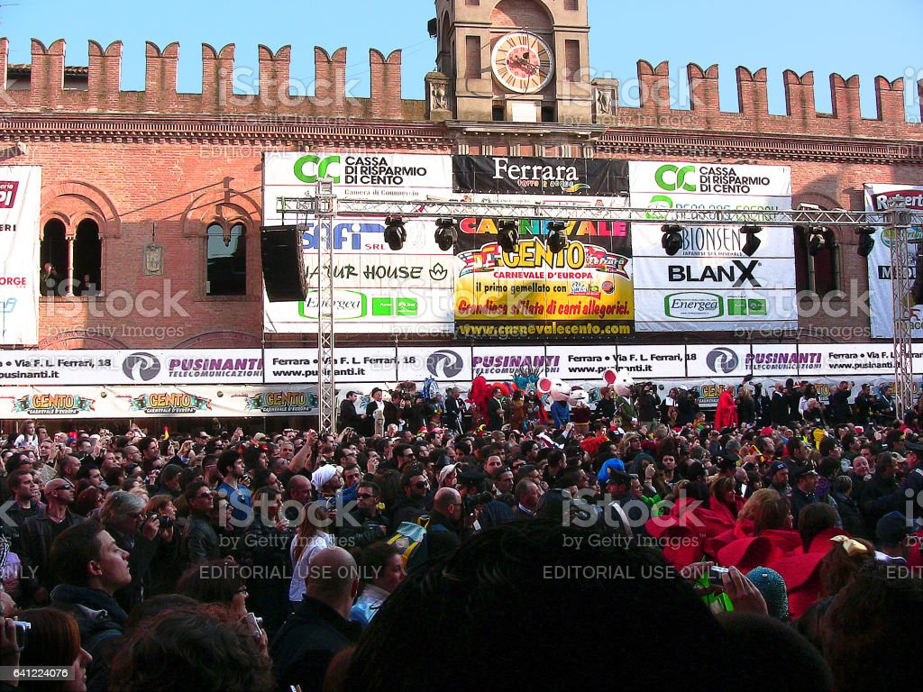 Cento, Emilia-Romagna, Italy - march 6, 2011: in the main square, crowd of spectators and dancers in red costume. Near the town hall, under the installation for lights, the stage for the awards. Many recognisable people and advertising posters. stock photo