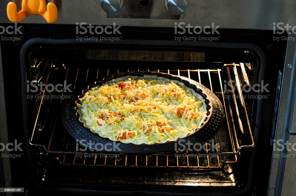 In the oven cooking the pie with cheese and tomatoes stock photo