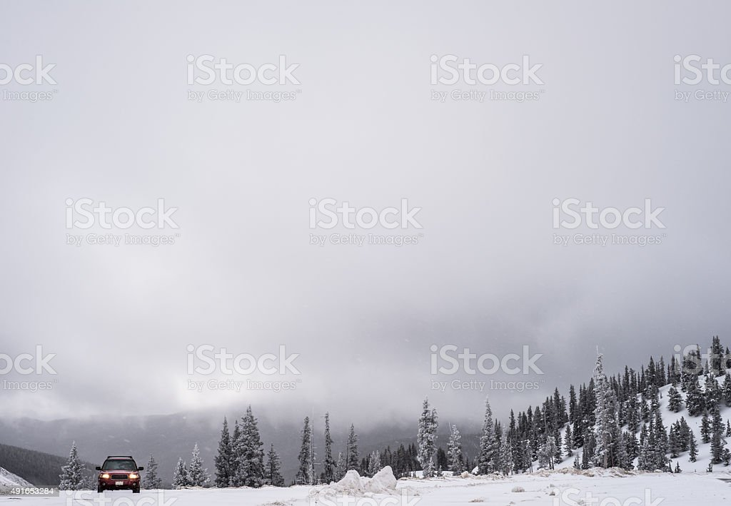 SUV in the snow on overcast day - wide shot stock photo