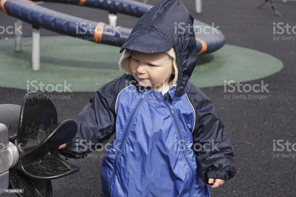 Small boy toddler playing in wet playground stock photo