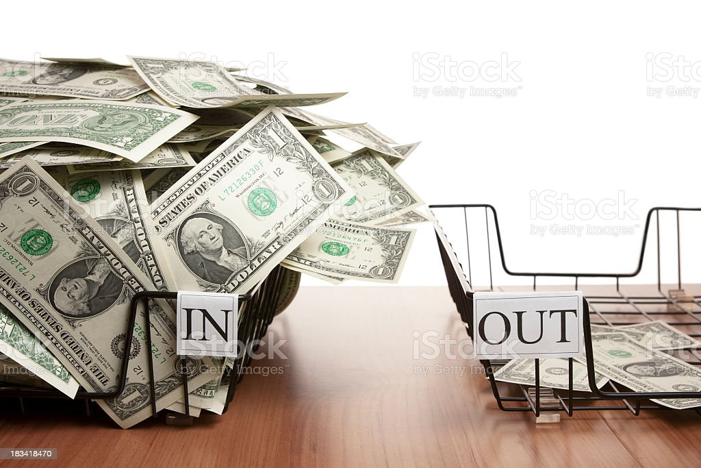 In tray overflowing with dollar notes and empty out tray stock photo