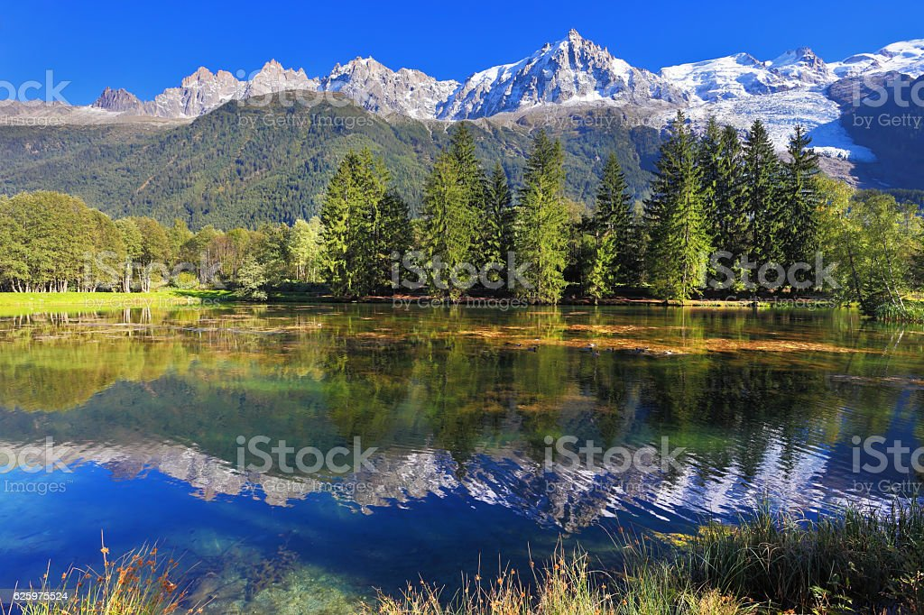 In water reflected snow-capped mountains stock photo