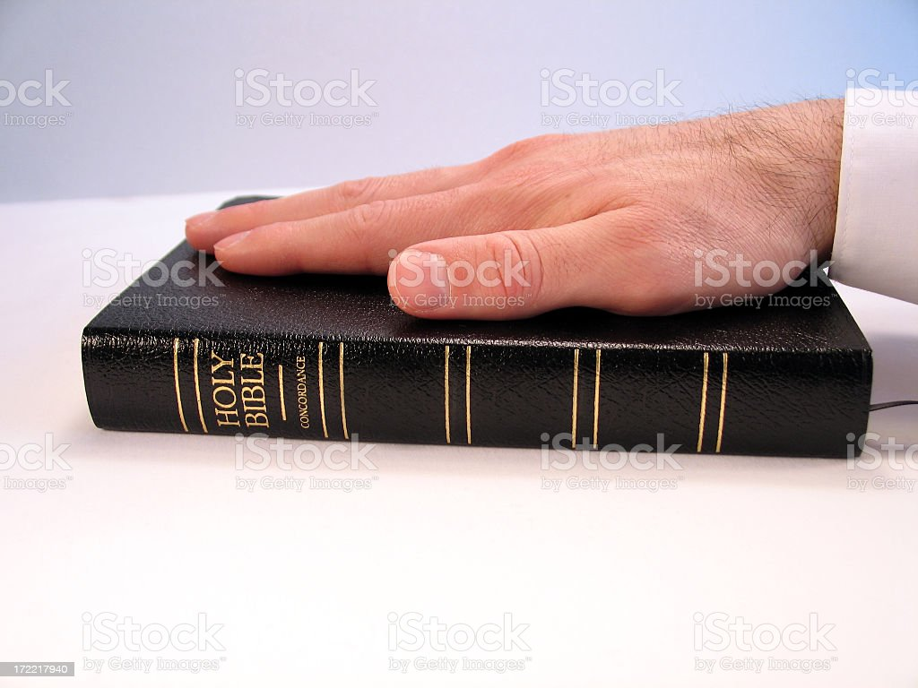 Inauguration Concept: Closeup of Hand on Bible While Taking Oath stock photo