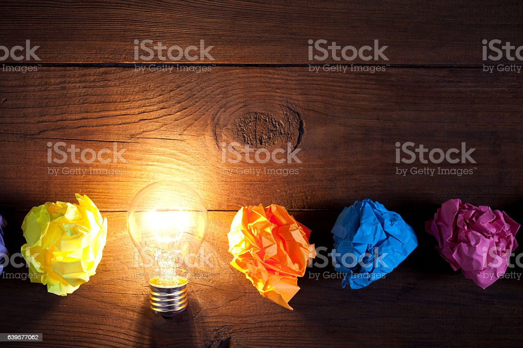 Incandescent bulb and colorful notes on old wooden table stock photo