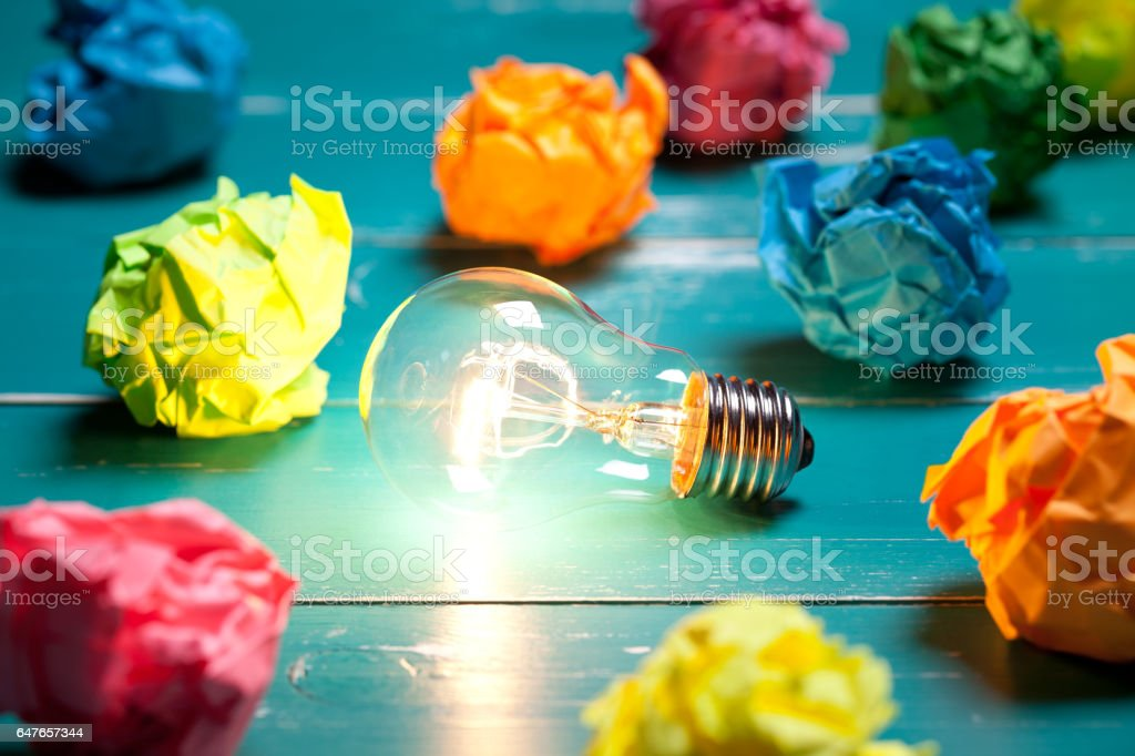 Incandescent bulb and colorful notes on turquoise wooden table stock photo