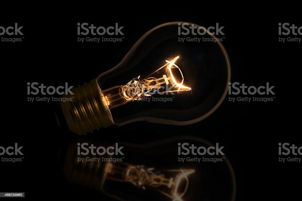 incandescent light bulb isolated on black background stock photo
