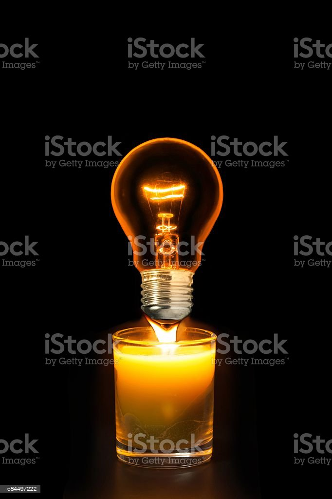 Incandescent lights bulb glowing in dark and glass candle stock photo