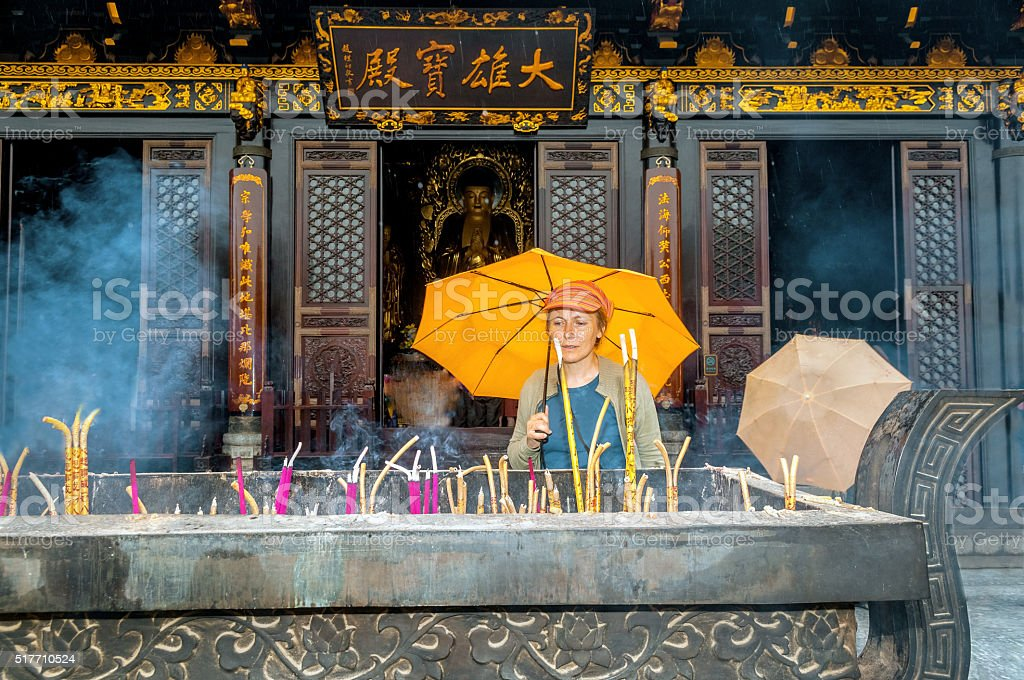 Incense in Buddhist Monastery,woman,in Xian, Shaanxi province, China. stock photo