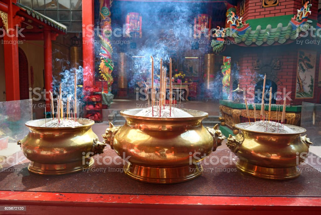 Incense sticks in the pot inside Chinese temple stock photo