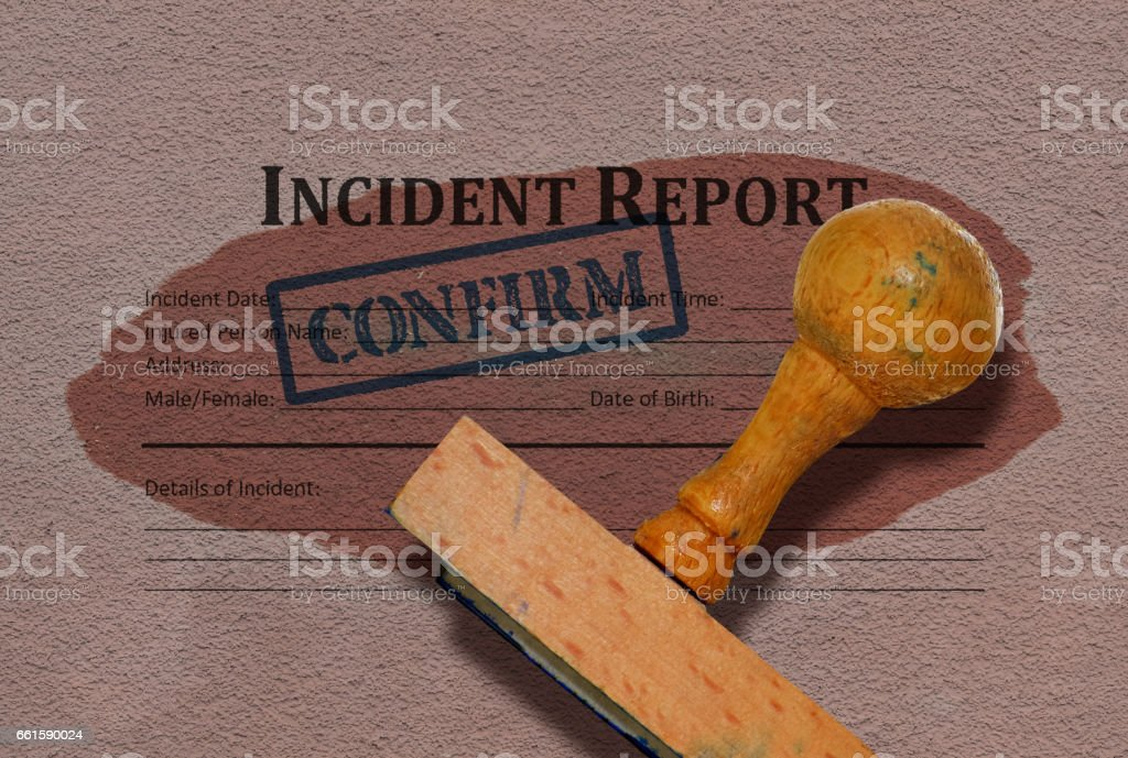 Incident report form and a wooden stamp on grunge background stock photo