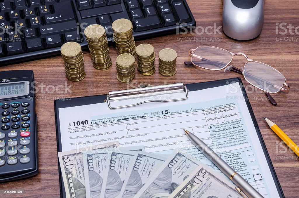1040EZ income tax form with money, pen on table stock photo