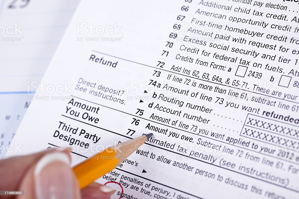 Income tax: forms, pencil pointing to 'Amount You Owe' royalty-free stock photo