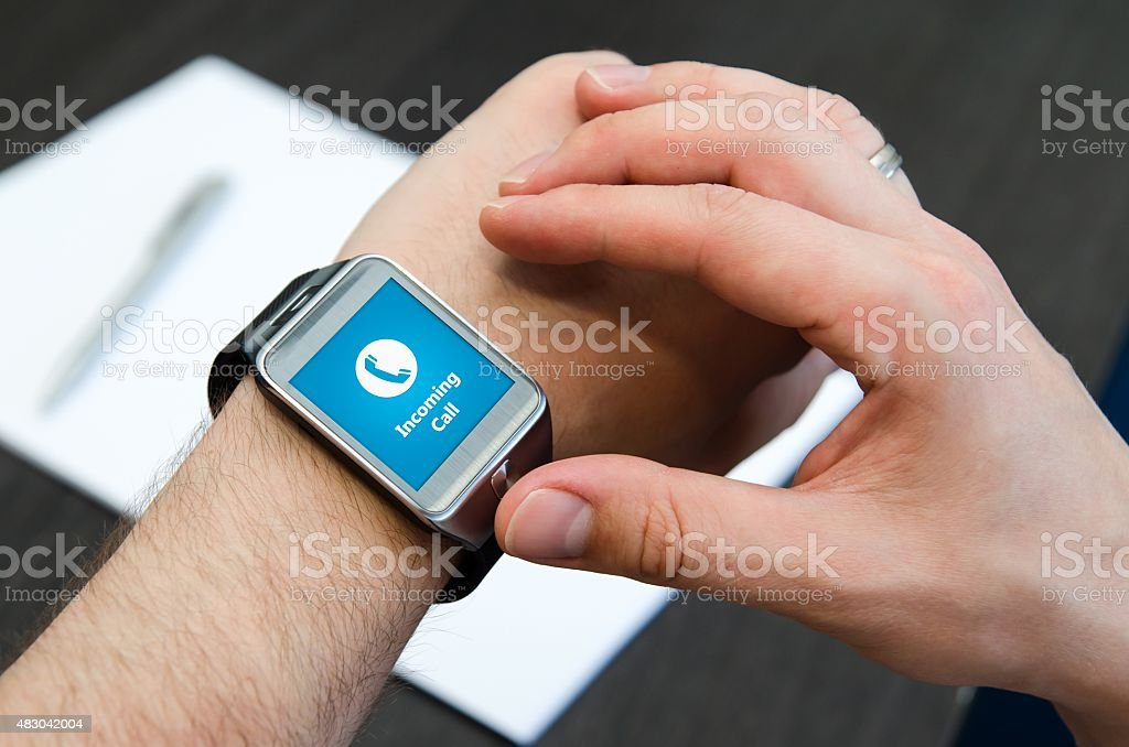 Incoming call notification on smart watch connected to smart pho stock photo