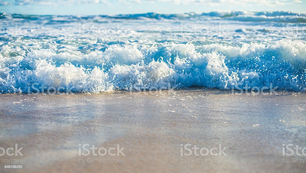 Incoming surf on golden sand stock photo