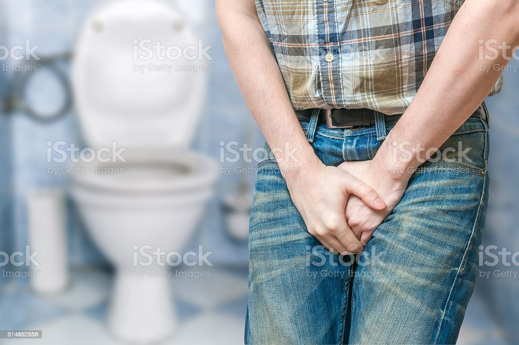 Incontinence concept. Man wants pee and is holding his bladder stock photo