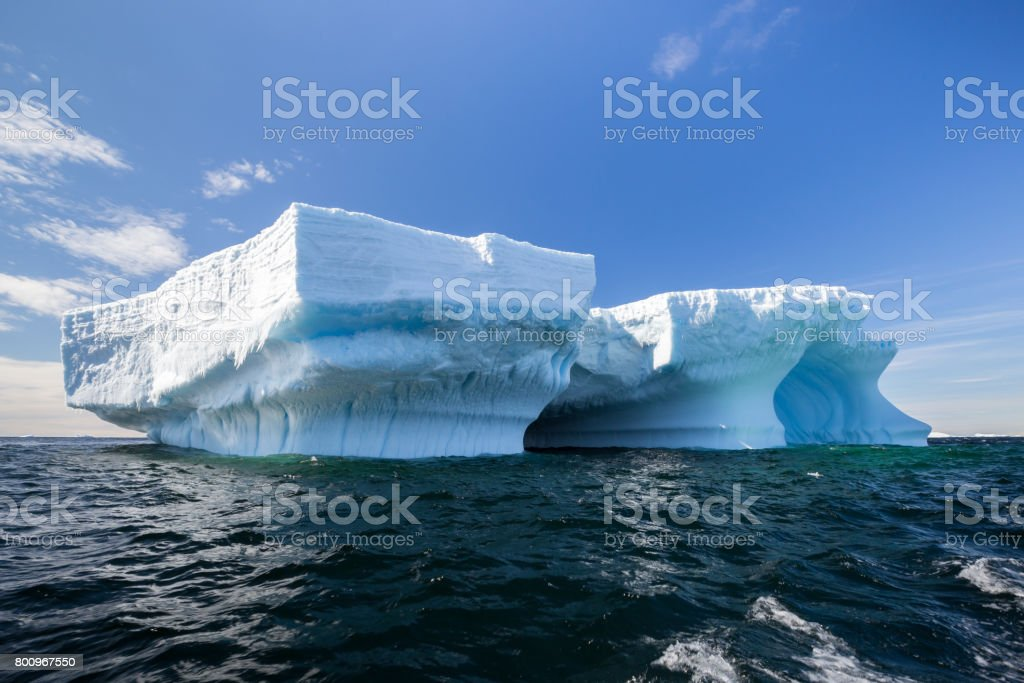 Incredibly large tabular iceberg floats in dark Antarctic waters stock photo