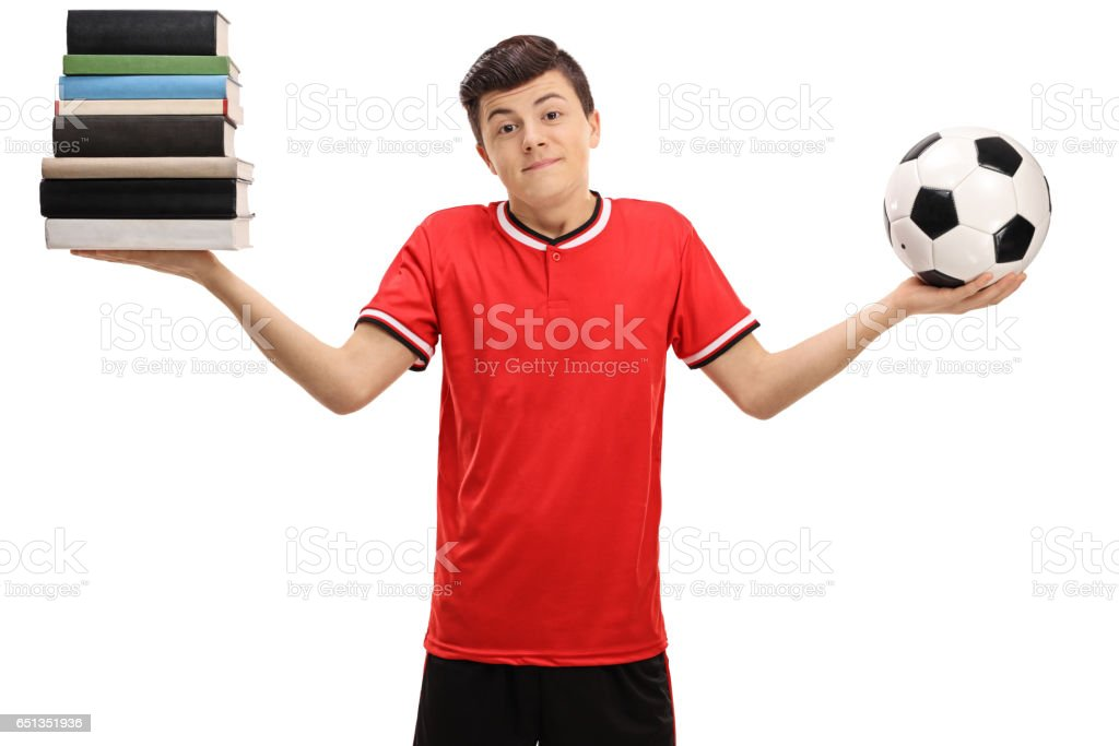 Indecisive teenage boy holding stack of books and football stock photo