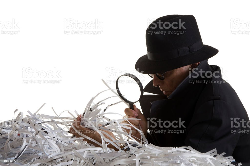 Indentity Thief sifts through shredded documents stock photo