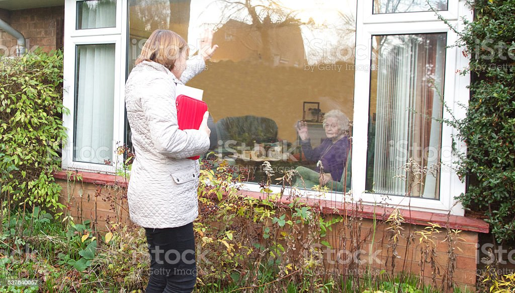 Independent living elderly client waving goodbye to her professional carer. stock photo