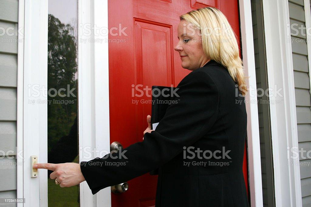 Independent saleswoman ringing doorbell stock photo