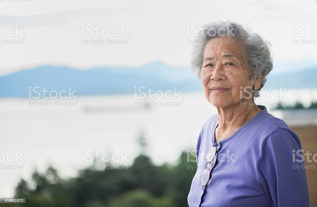Independent Senior Asian Woman Enjoying View from Apartment, Vancouver, Canada stock photo