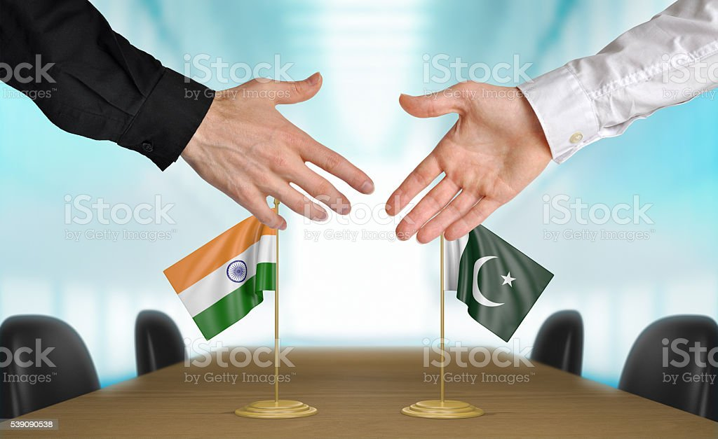 India and Pakistan diplomats shaking hands to agree deal stock photo