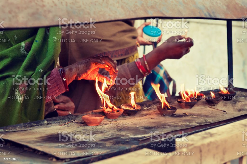 India, Rajasthan.Hand of old woman over the holy fire. stock photo