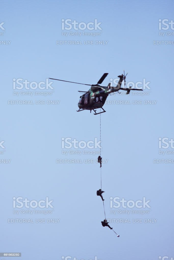 Indian Army Helicopter and hanging soldiers at Aero India stock photo
