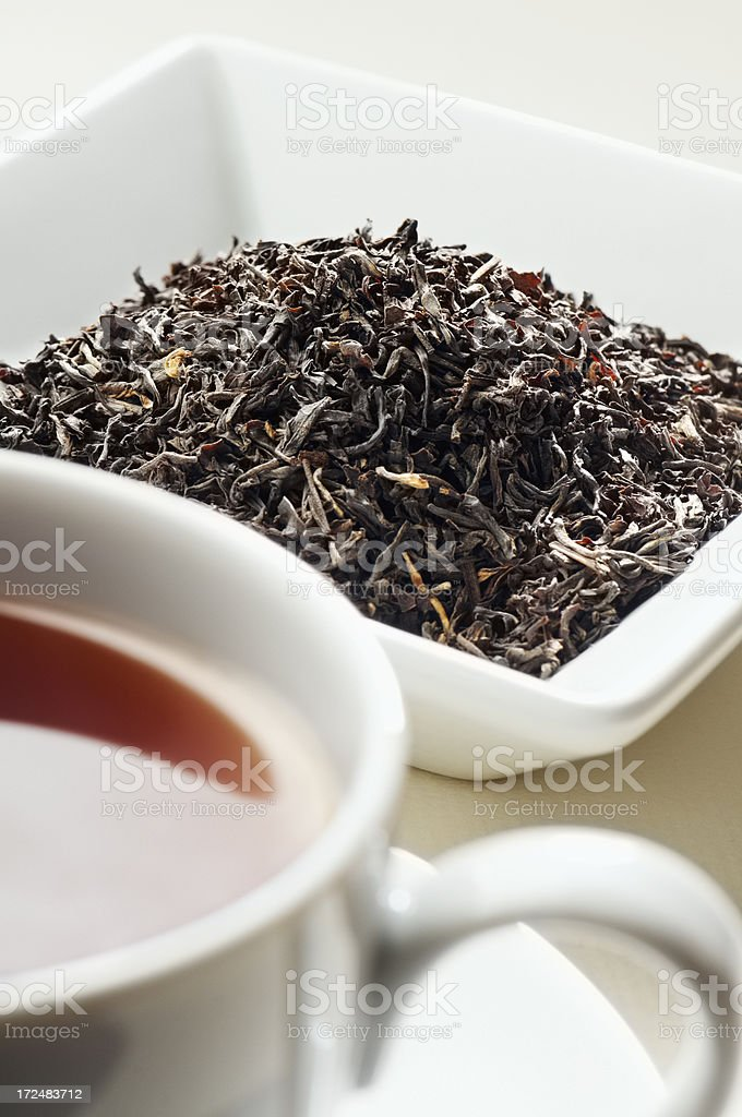 Indian Assam tea leaves behind cup of tea stock photo