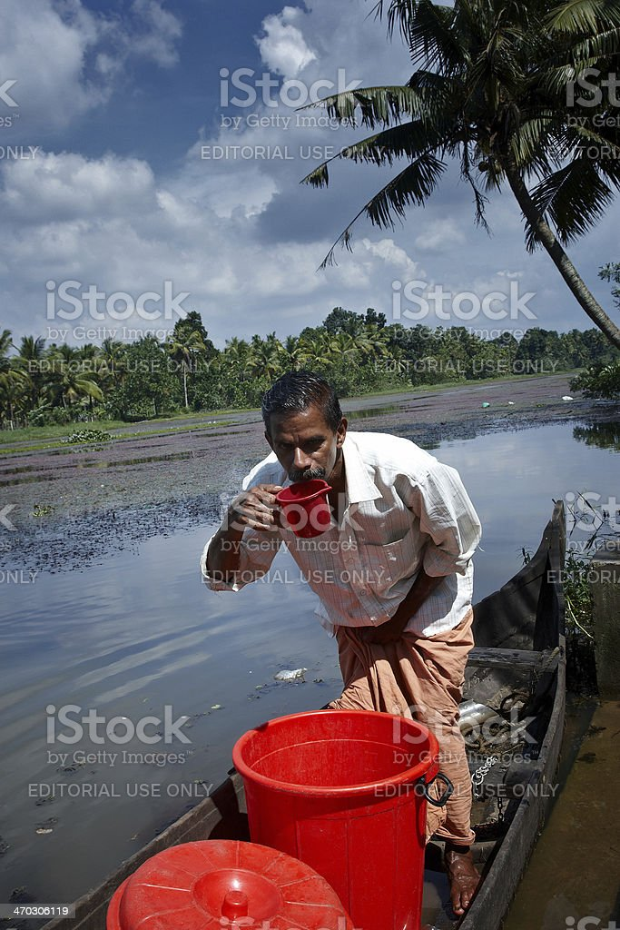 Indian boatman in the backwaters of Kerala tasting toddy royalty-free stock photo