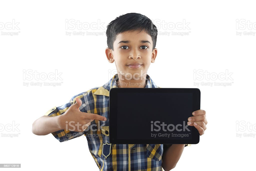 Indian boy holding tablet stock photo