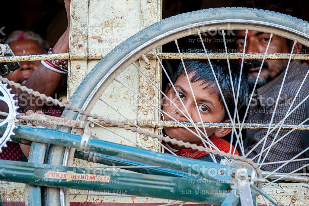 Indian boy looking outside window of train stock photo