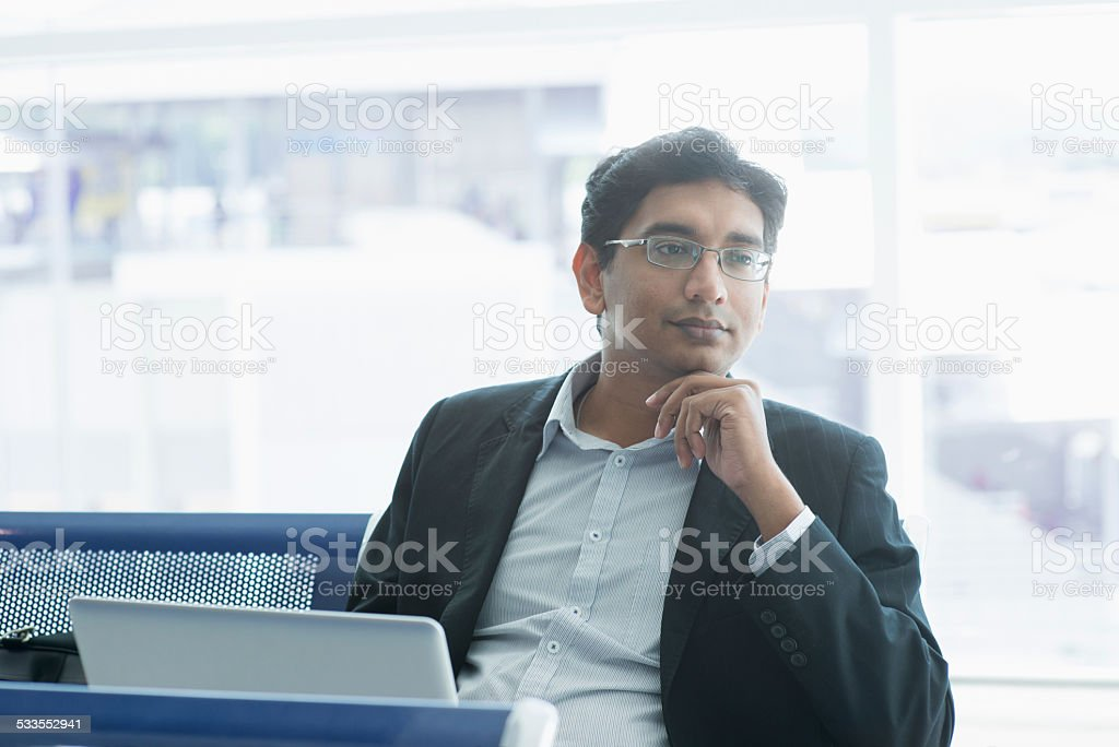 Indian business man having a thought at airport stock photo