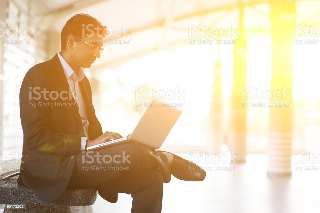 Indian businessman using laptop computer at railway station. stock photo