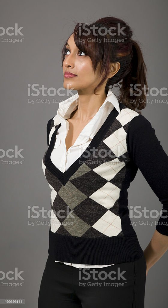 Indian businesswoman looking up with hands behind back royalty-free stock photo